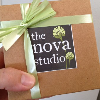 "Kraft Paper Box with a Green Ribbon and Square ""The Nova Studio"" Logo Sticker"