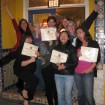 Alice Duvernell of Biophelia Botanicals with her Students Holding Certificates of Completion in Front of The Nova Studio in Point Richmond, CA, Making Funny Faces