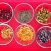 Rose Petals, Lavender, Chamomile, Orange Peel, Calendula Petals & Larkspur Petals in Glass Cups Against a Red Background